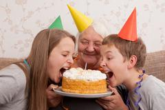 senior woman and its grandsons with birthday cake - stock photo