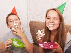 boy and teenage girl on birthday eat a cake - stock photo