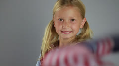 Cute Girl Scout Child Smiles at the Camera while Dressed in Uniform Waves Flag Stock Footage