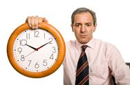 Stock Photo of mature handsome business man holding a clock