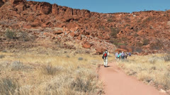 tourists walk in front of table mountain at twyfelfontein - stock footage