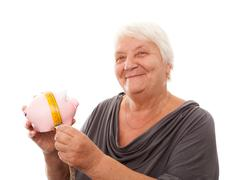 portrait of a happy mature woman holding piggy bank isolated against white - stock photo