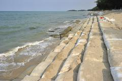 sand bags along the beach in songkra to protect from heavy surf and erosion, - stock photo
