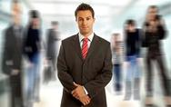 Stock Photo of young business man portrait smilling, among out of focus people