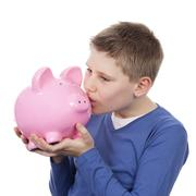 cute boy kissing pink piggybank - stock photo
