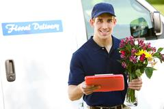 delivery: man ready to deliver flowers - stock photo