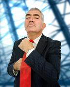 mature business man adjusting his red tie - stock photo