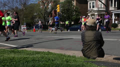 lady watching marathon runners  EDITORIAL USE ONLY - stock footage