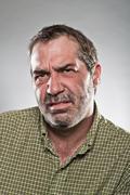 Mature caucasian man looking grumpy portrait Stock Photos