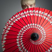 girl peeking over red parasol - stock photo