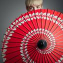 Stock Photo of girl peeking over red parasol