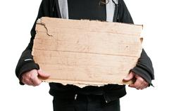 homeless man holding cardboard sign - stock photo