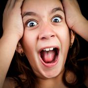 Girl screaming loudly on a black background Stock Photos