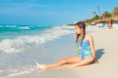 cute hispanic teen sitting on a sunny beach in cuba - stock photo