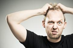 Caucasian man pulling out hair with frustration Stock Photos