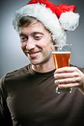 man wearing santa hat reluctantly toasting with beer - stock photo