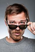 caucasian man looking over his sunglasses - stock photo