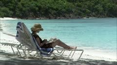 Lady on sun lounger on beach Stock Footage