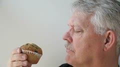 Man eats blueberry muffin Stock Footage