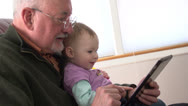 Grandfather and granddaughter playing with a tablet Stock Footage