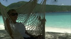 Lady in hammock on beach Stock Footage