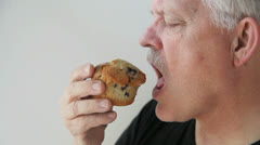 Man has a muffin with coffee Stock Footage