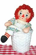 old rag doll in basket - stock illustration