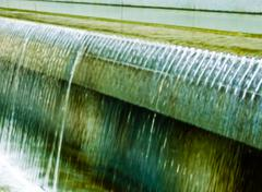 Water flowing over edge of granite wall into a pool of shallow water Stock Photos