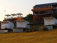 white tents and resort building in pai, mae hong son and meadow field in sunr - stock photo