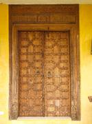 Antique moroccan style wooden door  on yellow wall Stock Photos