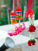 Fresh natural flower garland and artificial  flower garland hanging together Stock Photos