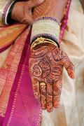 bride's hand with henna and bangles - stock photo