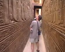 Tourists walking down a narrow passage with hieroglyphics Stock Footage