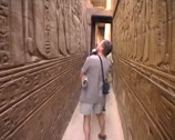 Stock Video Footage of Tourists walking down a narrow passage with hieroglyphics