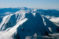 Vuoren huipulla lumen peitossa, ilmakuva Kuvituskuvat