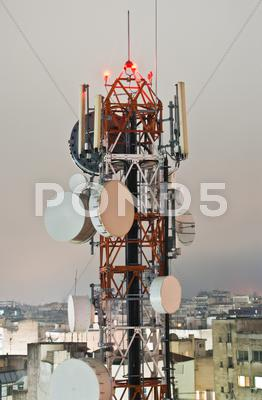 Stock photo of telecommunications tower by night, aerial view