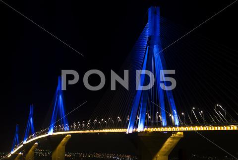 Stock photo of rio-antirio bridge over sea, illuminated at night.