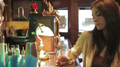Beautiful woman drinks beer in a bar - dolly Stock Footage