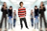 Stock Photo of young casual boy full body, among some out of focus people