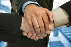 Close up of three men hands together in a deal, studio picture Stock Photos