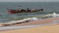 Fishermen unload fresh catch of fish on beach - Kerala India Stock Footage