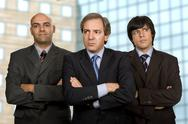 Stock Photo of team of three business men standing pensive
