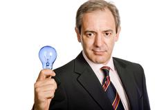 Mature business man with a lamp isolated on white Stock Photos