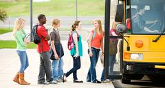 school bus: line of students boarding bus - stock photo
