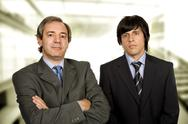 Stock Photo of two young business men portrait, focus on the right man