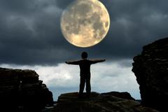 Woman with arms wide open and the moon Stock Photos