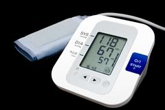 Digital blood pressure monitor isolated on black Stock Photos