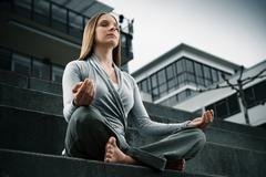 Young girl meditating, sitting yoga exercise in a modern environment - stock photo