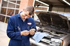 mechanic: couting money from scamming customer - stock photo