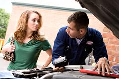 mechanic: man explaining about oil filters - stock photo